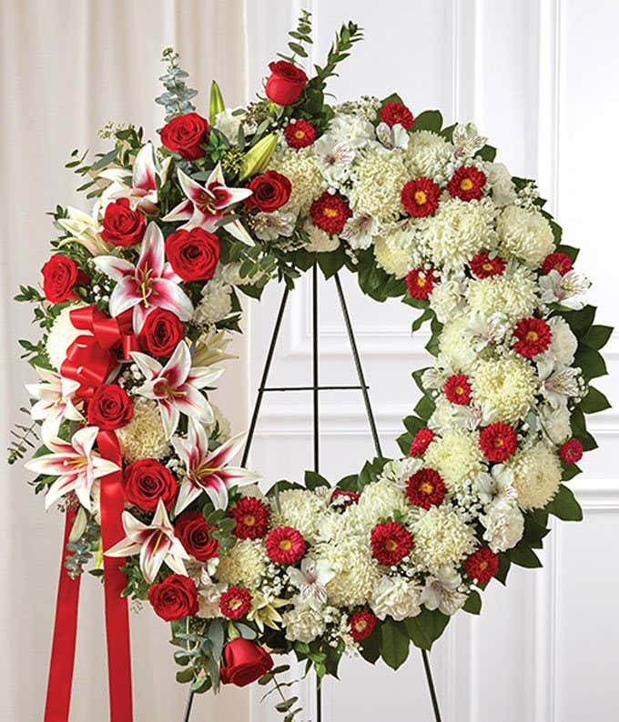 Roses and mums arranged by a florist in a sympathy wreath