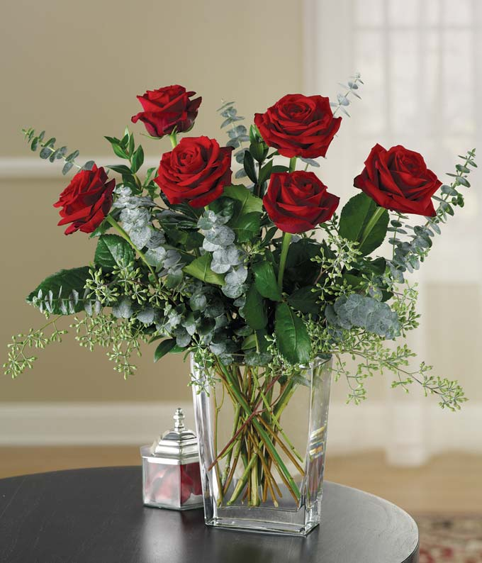 Red roses and eucalyptus in a modern glass vase
