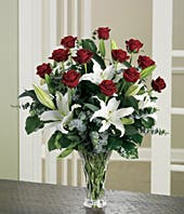 Long stem red roses delivered with white lilies in glass vase