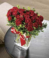 Red spray roses delivered by florist in glass vase