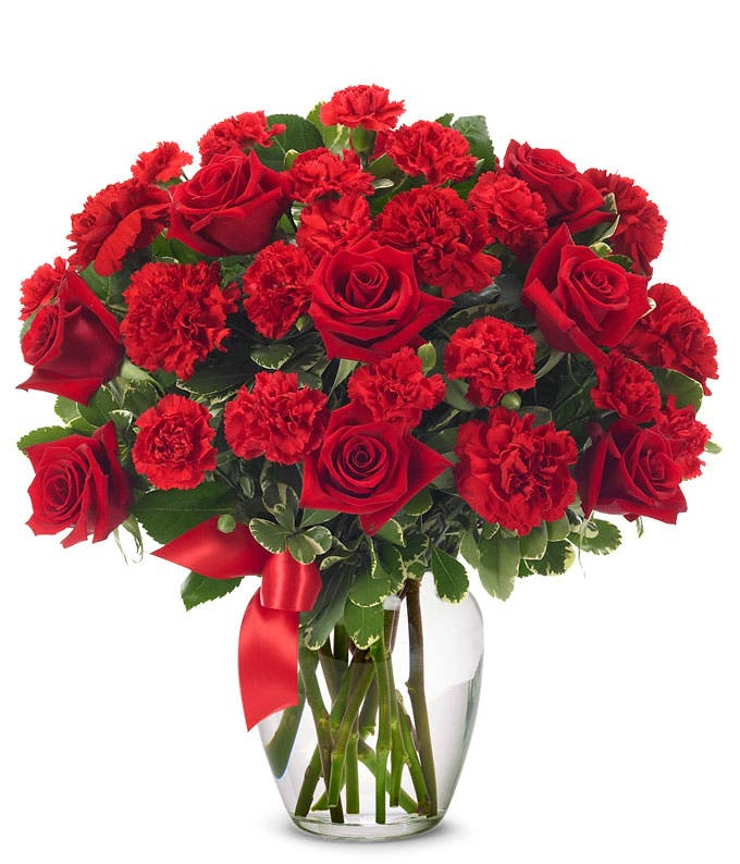 Red carnations and red roses in a glass vase