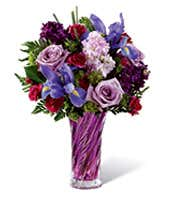 Purple roses are arranged with purple daisies, iris and gilly flowers in a purple vase
