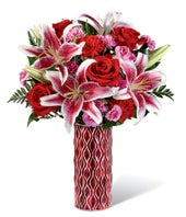 Pink asiatic lilies, red roses and red carnations in colorful vase