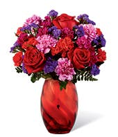 Red rose and hot pink carnations in modern red vase