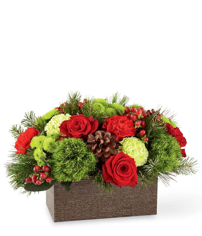Red roses in a rectangle vase with hypericum berries for a Christmas bouquet