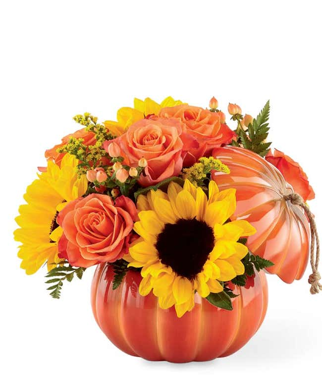 pumpkin vase with sunflowers and orange roses