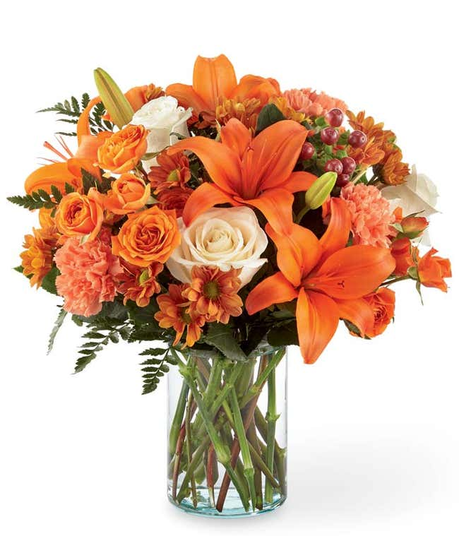 Orange lilies, cream roses and orange roses are arranged for Fall delivery