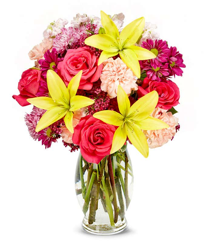 Yellow lilies, pink roses, pink daisies all in a vase
