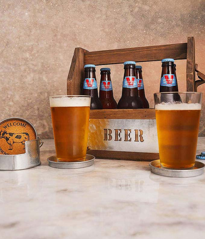 Wood beer carries, cork coasters and two beer glasses in a beer gift basket