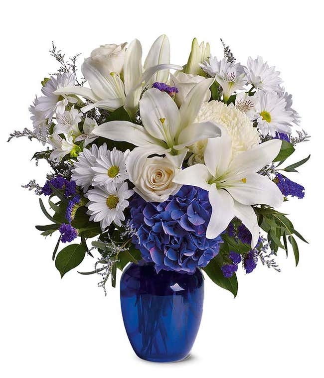Blue hydrangea, white roses and white oriental lilies in a blue vase