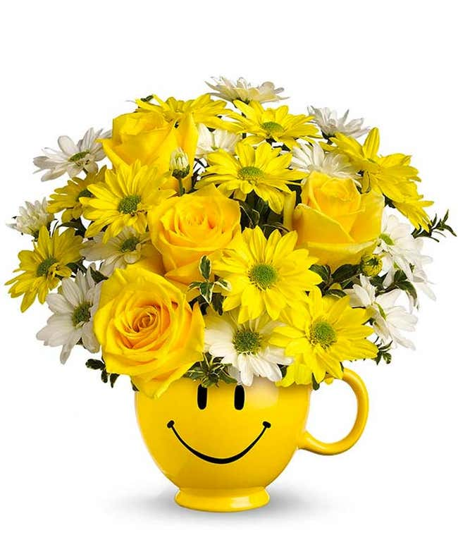 Yellow roses and bright daisies in a yellow smiley face mug