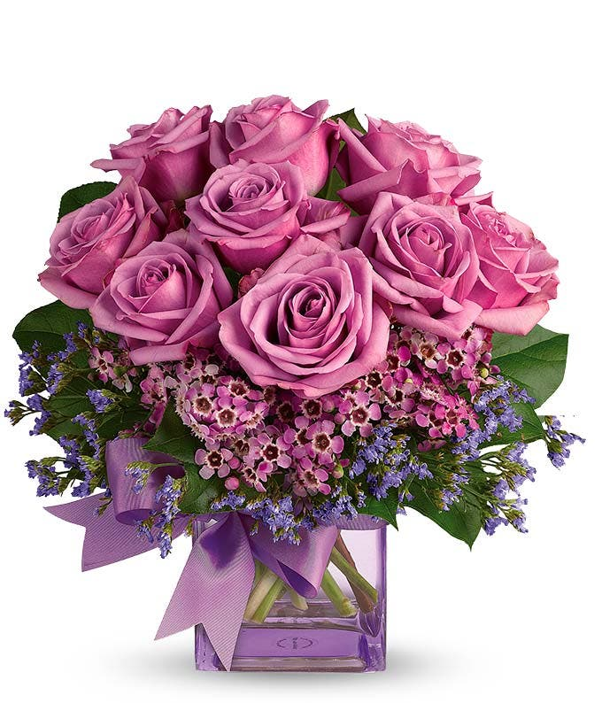 Purple roses in square glass vase
