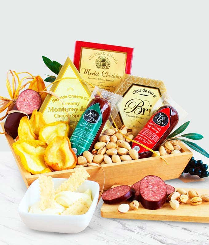 Pistachios, dried fruit, sausage and cheese in a wooden crate